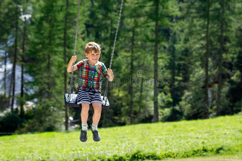 Funny kid boy having fun with chain swing on outdoor playground while being wet splashed with water. Child swinging on summer day. Active leisure with kids stock photo