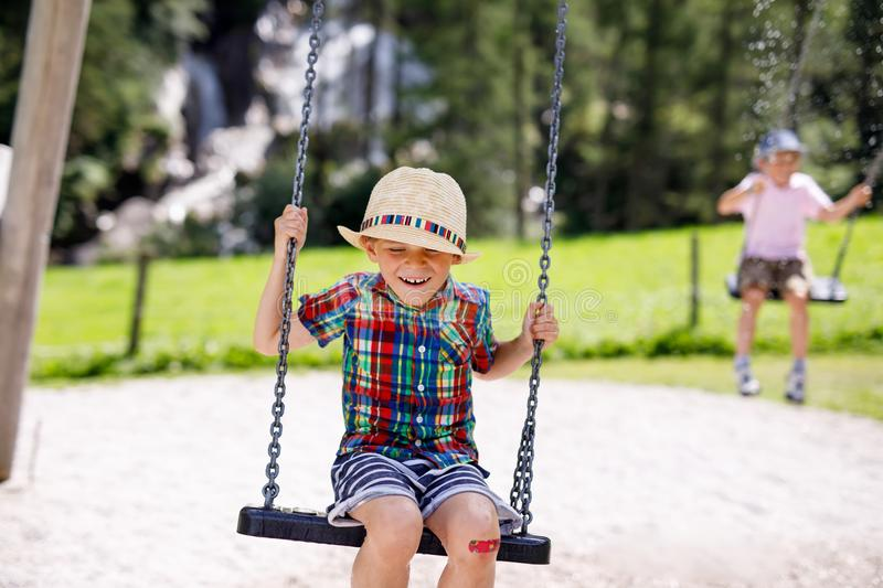 Funny kid boy having fun with chain swing on outdoor playground while being wet splashed with water. Two kids boys having fun with chain swing on outdoor stock photos