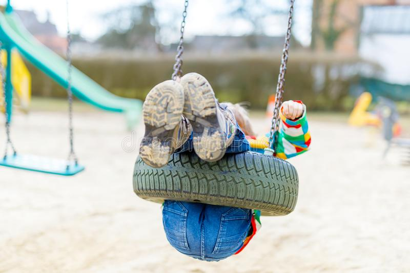 Funny kid boy having fun with chain swing on outdoor playground. Child swinging on warm sunny spring or autumn day. Active leisure with kids. Selective focus royalty free stock photo