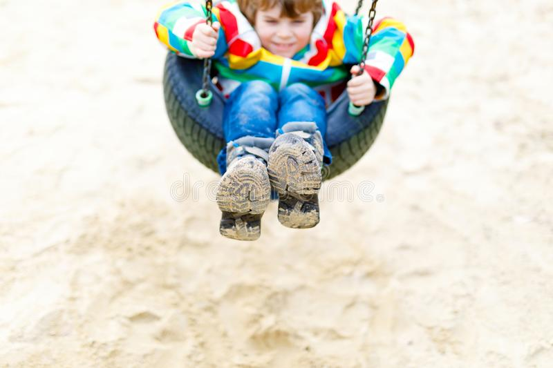 Funny kid boy having fun with chain swing on outdoor playground. Child swinging on warm sunny spring or autumn day. Active leisure with kids. Boy wearing stock images