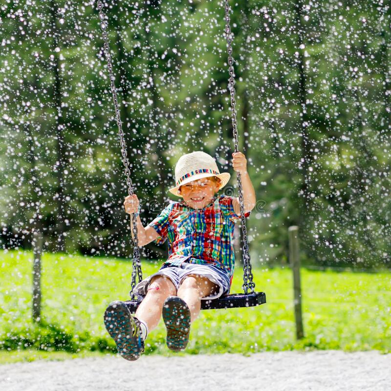 Free Funny Kid Boy Having Fun With Chain Swing On Outdoor Playground While Being Wet Splashed With Water. Child Swinging On Stock Photo - 177692830