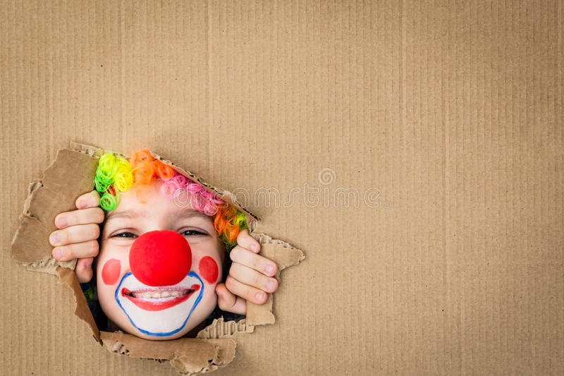 Funny kid clown playing indoor. Funny kid clown looking through hole on cardboard. Child playing at home. 1 April Fool`s day concept. Copy space stock photo