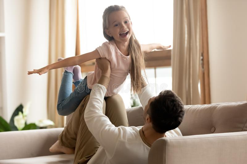 Funny kid daughter flying in fathers hands playing at home stock image