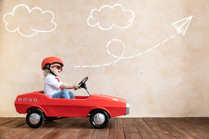 Funny kid driving toy car at home royalty free stock photo