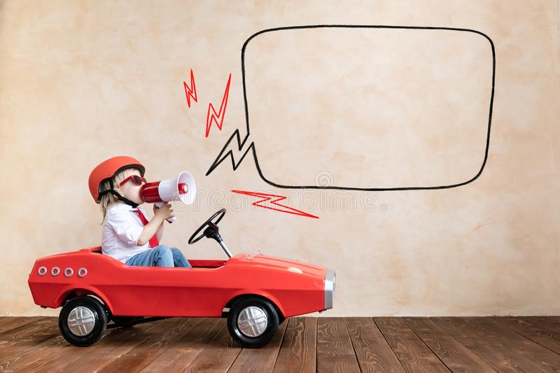 Funny kid driving toy car at home stock photos