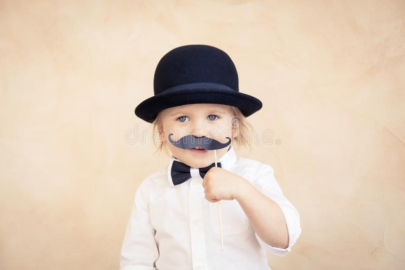 Funny kid with fake paper mustache. Funny kid with fake paper moustache. Happy child playing in home. Father's day concept royalty free stock photo