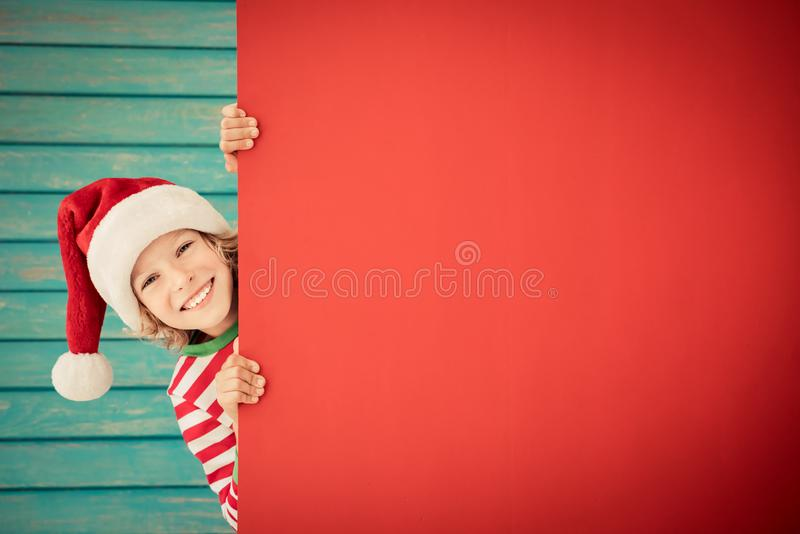 Funny kid holding cardboard banner blank. Child playing at home. Christmas holiday concept. Copy space stock image