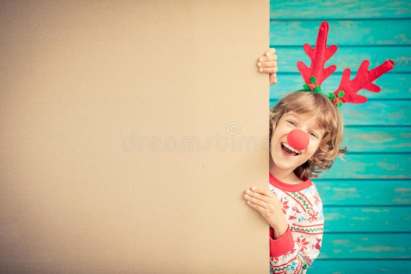 Funny kid holding cardboard banner blank. Child playing at home. Christmas holiday concept. Copy space royalty free stock images
