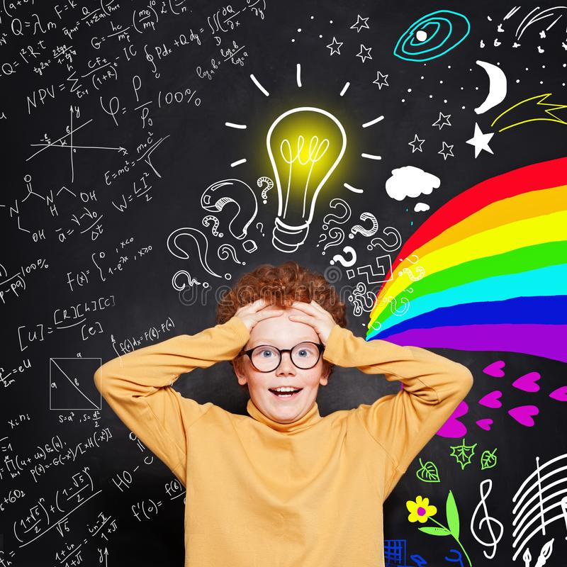 Funny kid. How do I choose the right career path? Child student boy with science and art pattern on blackboard background stock images