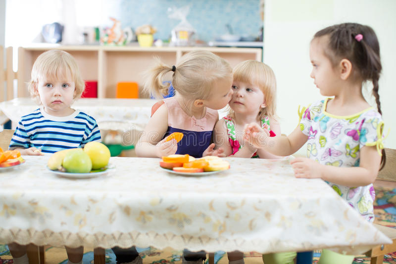 Funny kid kissing another one in day care centre royalty free stock photo