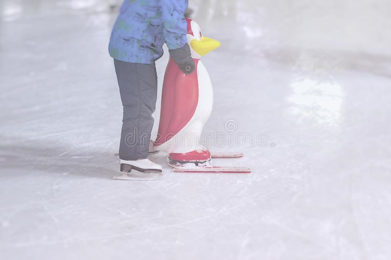 Funny kid outdoors in the park on skating rink in winter park stock photo
