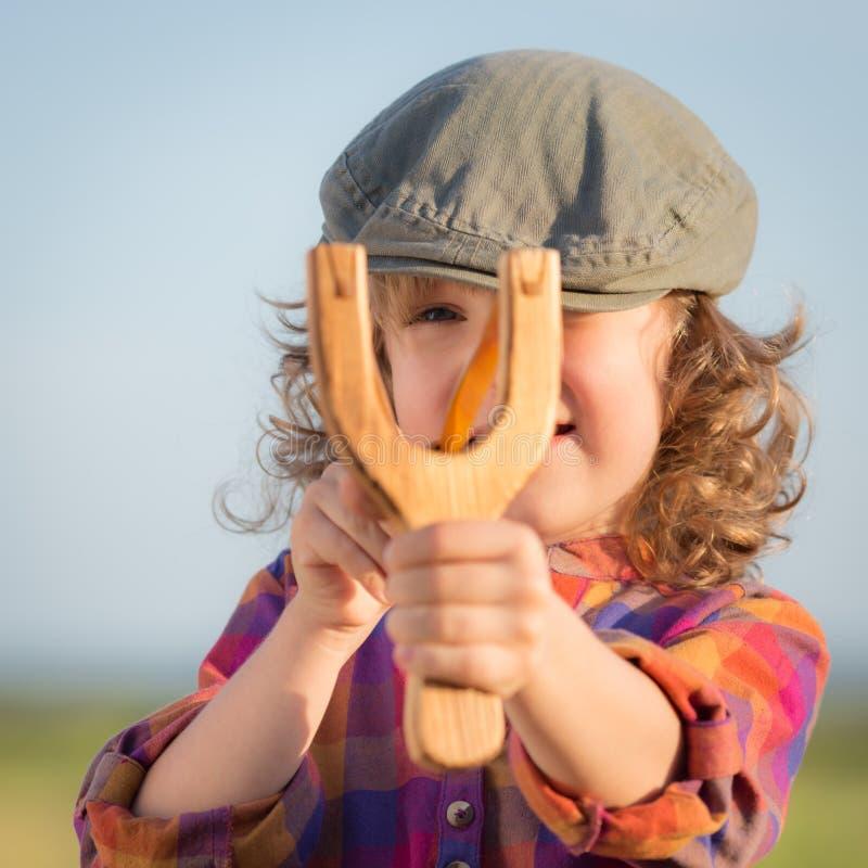 Funny kid shooting wooden slingshot stock photo