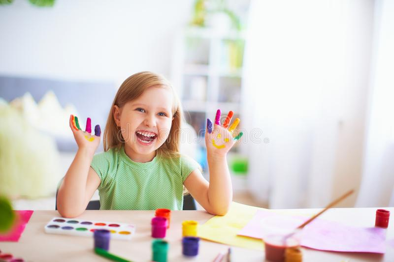 Funny kid show their palms the painted paint. creative classes fine arts. child girl laugh. happy kid in drawing school. Happy laughing little girl sitting at a stock photos