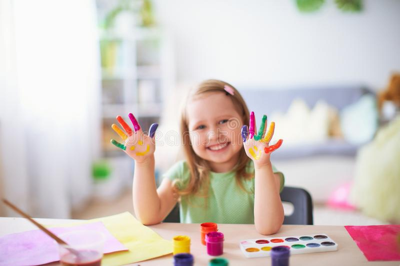 Funny kid show their palms the painted paint. creative classes fine arts. child girl laugh. happy kid in drawing school. Happy laughing little girl sitting at a royalty free stock photo
