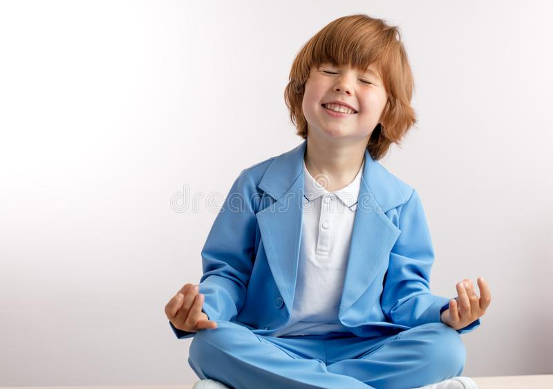 Funny kid in stylish suit is doing lotus pose. yoga for kids concept. White background. copy space stock photography