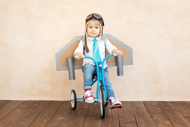 Success, imagination and innovation technology concept. Funny kid with toy jet pack. Happy child playing at home. Success, imagination and innovation technology stock image