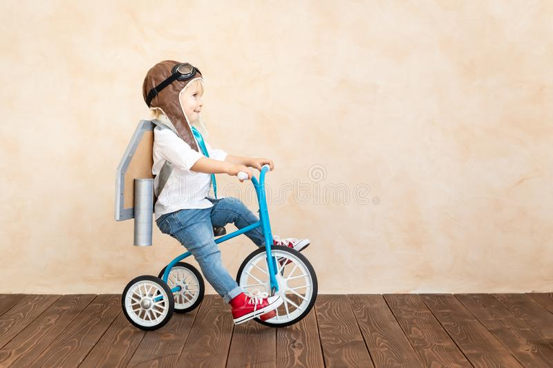 Success, imagination and innovation technology concept. Funny kid with toy jet pack. Happy child playing at home. Success, imagination and innovation technology stock photo