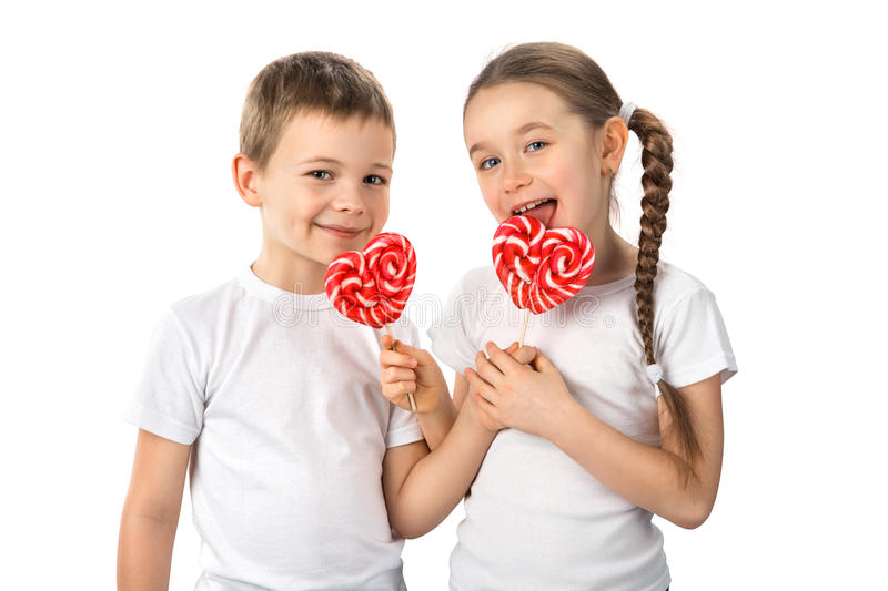 Funny kids with candy red lollipops in heart shape isolated on white. Valentine`s day. Cute kids little boy and girl in white T-shirts with candy red lollipops royalty free stock photography