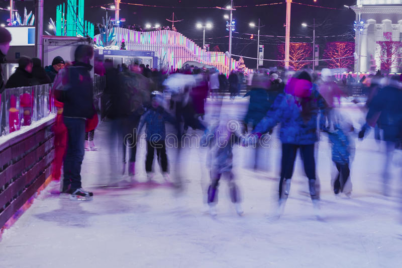 Funny kids, families together in evening time outdoors in the park on winter skating rink. Blurred photo stock image