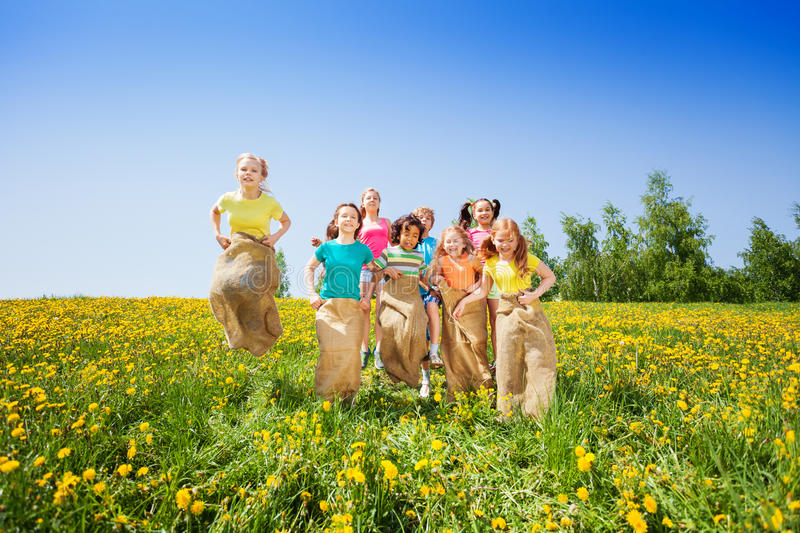 Funny kids jumping in sacks playing together. In summer royalty free stock image