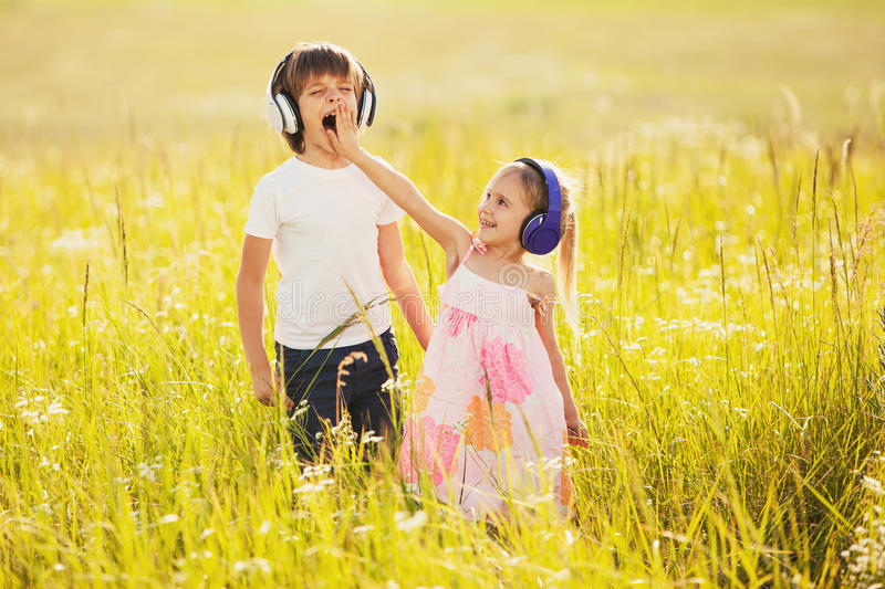 Funny kids listen music on nature stock images