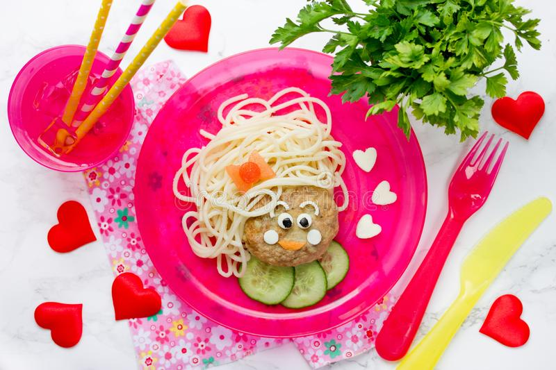 Funny kids lunch spaghetti pasta with meatball. In shape of girl face royalty free stock photos
