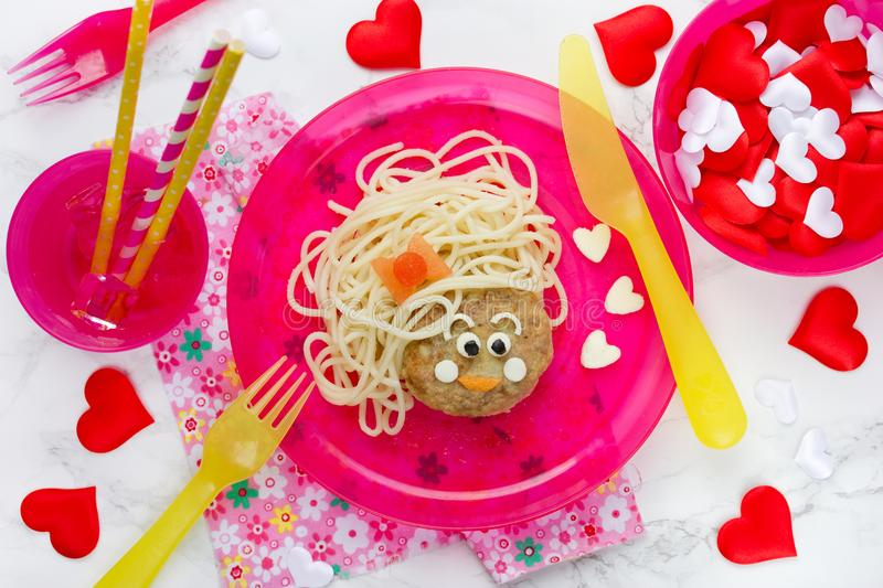 Funny kids lunch spaghetti pasta with meatball. In shape of girl face stock photos