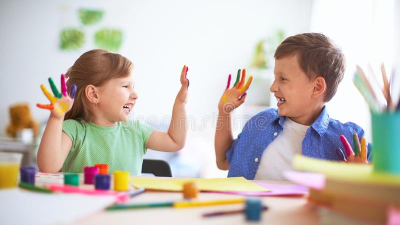 Funny kids show their palms the painted paint. creative classes fine arts. two children a boy and a girl laugh. selective focusing. On the palm. happy kids in stock photos