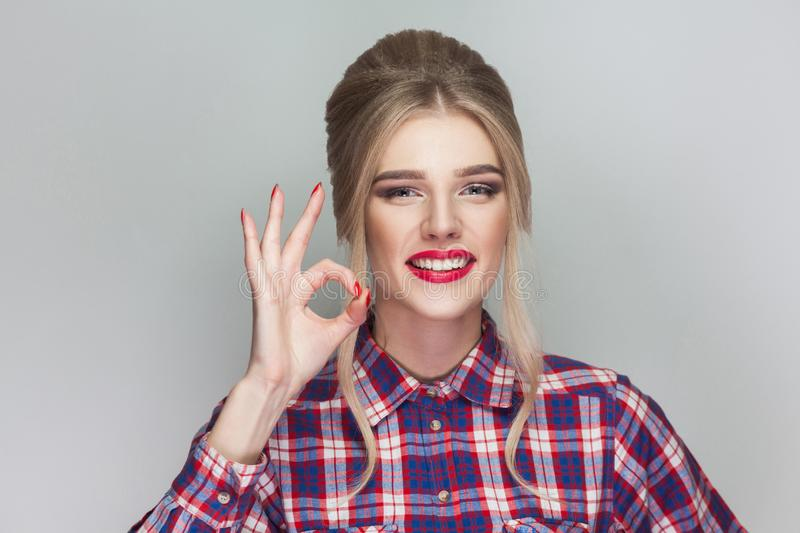 funny kissing beautiful girl with pink checkered shirt, collected updo hairstyle and makeup standing and showing Ok sign and look royalty free stock photos