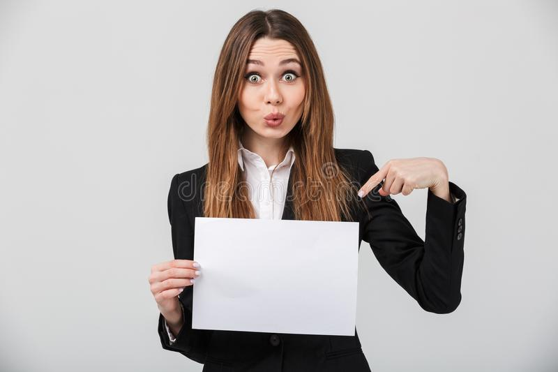 Funny lady grimacing and pointing at white sheet isolated. Funny pretty lady dressed in suit grimacing and pointing at blank white sheet isolated over grey wall royalty free stock photos