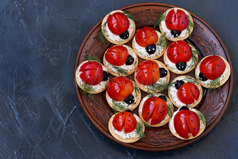 Funny Ladybird Snack Appetizer with Tomato on Crackers with cheese on a dark background royalty free stock photos