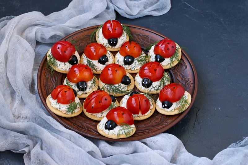 Funny Ladybird Snack Appetizer with Tomato on Crackers with cheese on a dark background. Copy space stock images
