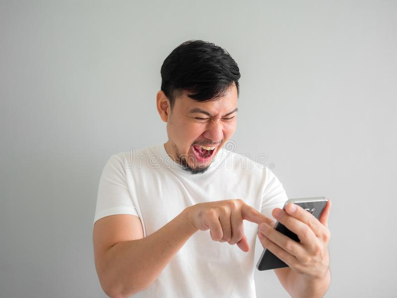 Funny laugh face of man watching funny video clip share in social in the smartphone. royalty free stock photo