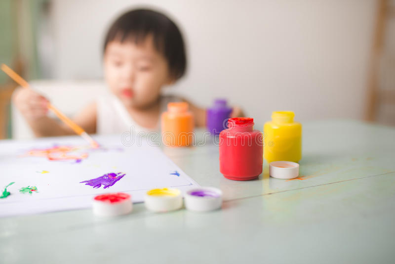 Funny laughing asian baby girl drawing with colorful pencils at. Home stock photo