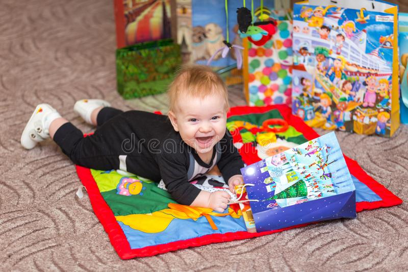 Funny laughing baby boy with present bag on the carpet stock image