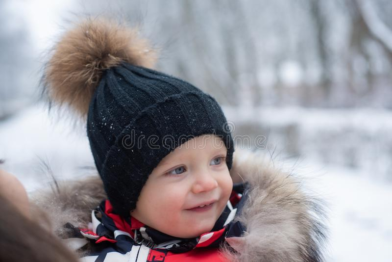 Funny laughing baby in winter outside. Cute toddler kid in a warm snowsuit and hat discovered winter forest. Snow, red stock images