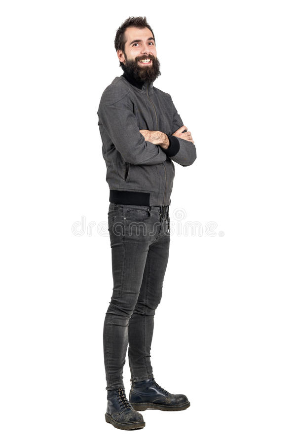Funny laughing bearded man in tight jeans and army boots looking at camera. Full body length portrait isolated over white studio background royalty free stock images