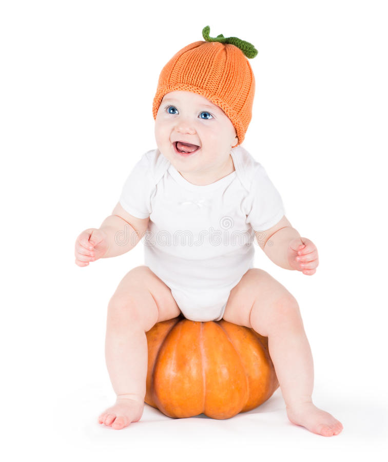 Funny laughing little baby on huge pumpkin royalty free stock photography
