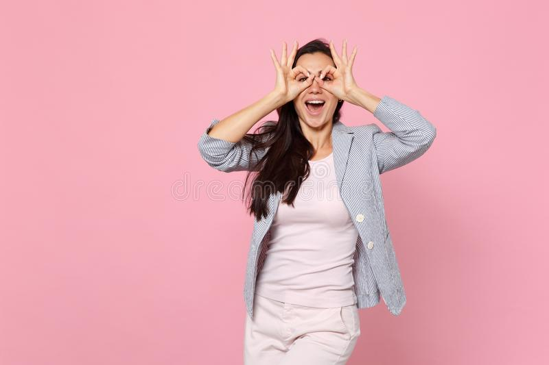 Funny laughing young woman in striped jacket holding hands near eyes, imitating glasses or binoculars isolated on pink stock images