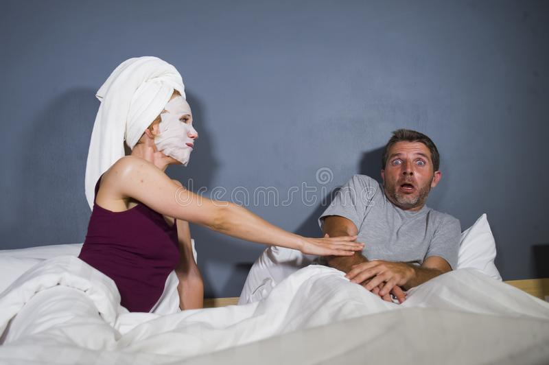 Funny lifestyle portrait of man and woman featuring weird married couple with wife in head towel and makeup face mask demanding se royalty free stock images