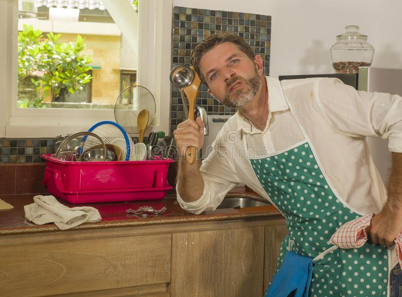 Funny lifestyle portrait of mid adult unhappy and stressed man in kitchen apron feeling frustrated and upset overwhelmed by stock photography