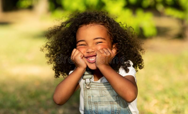 Funny little afro girl touching cheeks and having fun stock photography