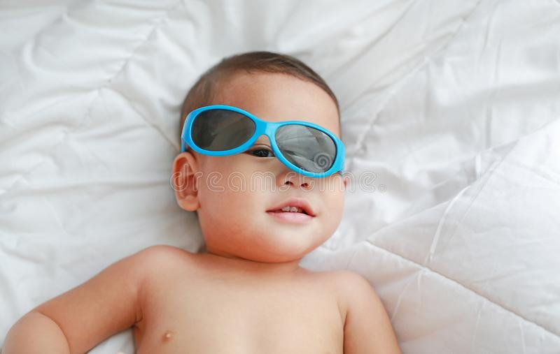 Funny little Asian baby boy with sunglasses lying on white blanket on bed. Above view.  royalty free stock photos