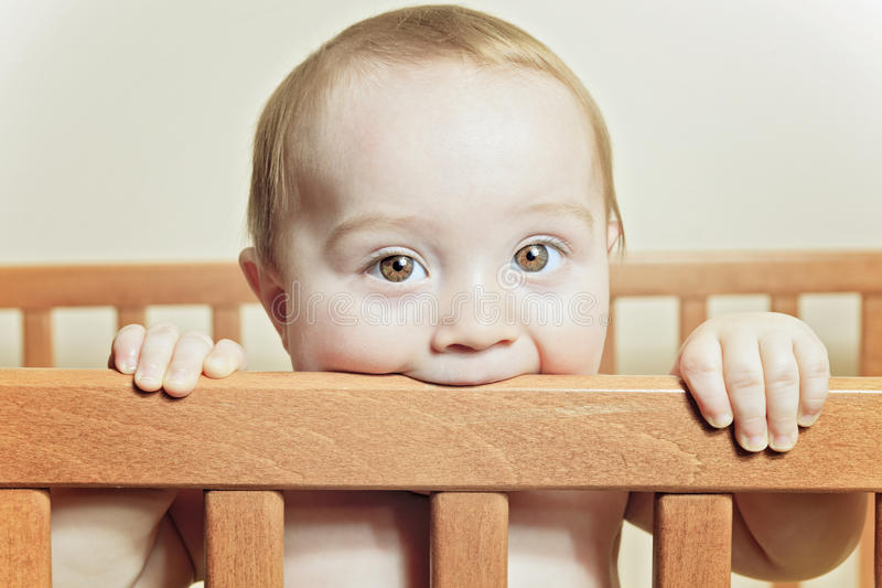 Funny little baby with beautiful standing in a round white crib royalty free stock image