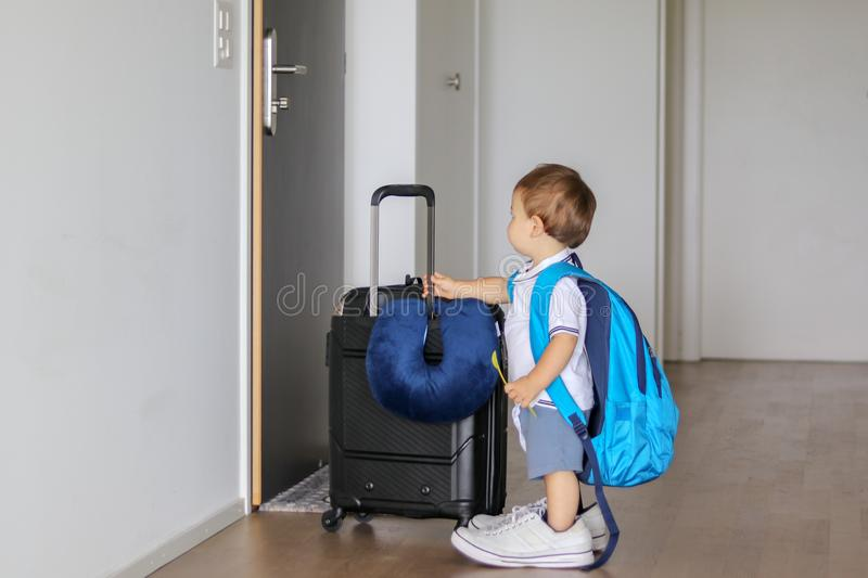 Funny little baby boy in fathers shoes with big backpack, suitcase and spoon in his hand staying in hallway looking at door ready. To leave, prepared for travel stock photography