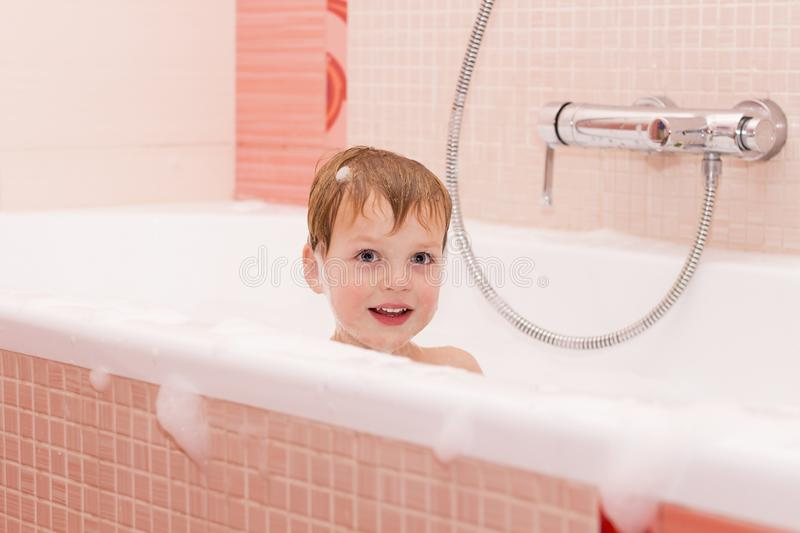 Funny little baby boy playing with foam in a bath tub royalty free stock images