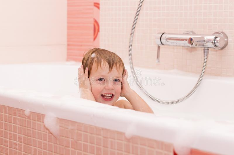Funny little baby boy playing with foam in a bath tub royalty free stock image