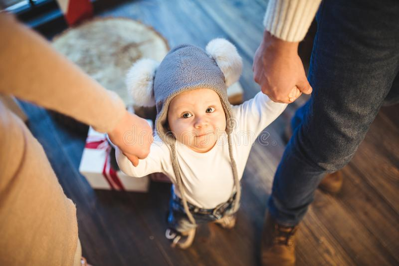 Funny little baby boy 1 year old learning walk home in winter in a decorated New Year house. Young family dad and mom hold by the royalty free stock image