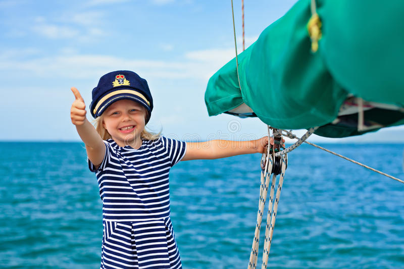 Funny little baby captain on board of sailing yacht royalty free stock photos
