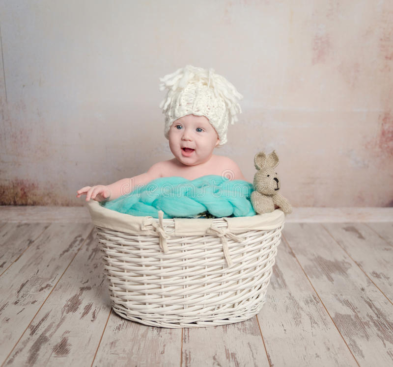 Funny little baby sitting in basket. Funny little baby sitting in wicker basket with toy-hare royalty free stock image